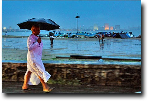 Walking in the rain near the temporary fishing village on Chowpatty beach
