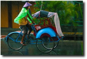Becak driver working in the rain