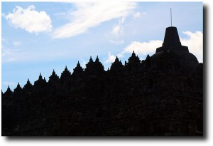 The rows of carvings and stupas are silhouetted against the sky