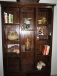 The new bookcase we just bought, at the head of the dining room table, complete with a cat chilling in it