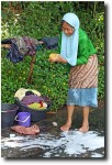 Old women wash laundry in the stream.