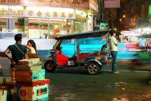 Category - Open: A tuk tuk waits for customers amid the bustle of a Bangkok Chinatown evening.